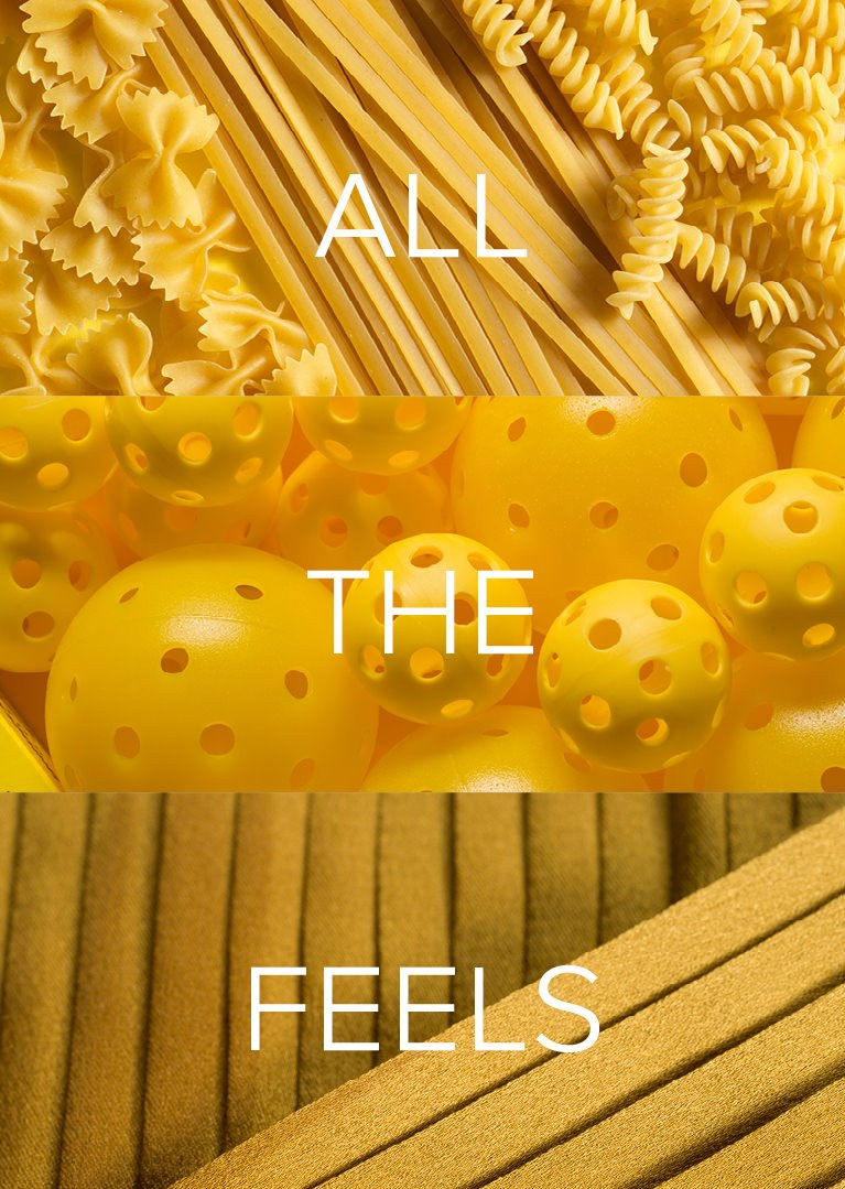 Image of yellow pasta, yellow plastic balls with holes, and yellow pieces of fabric with All The Feels written in white text